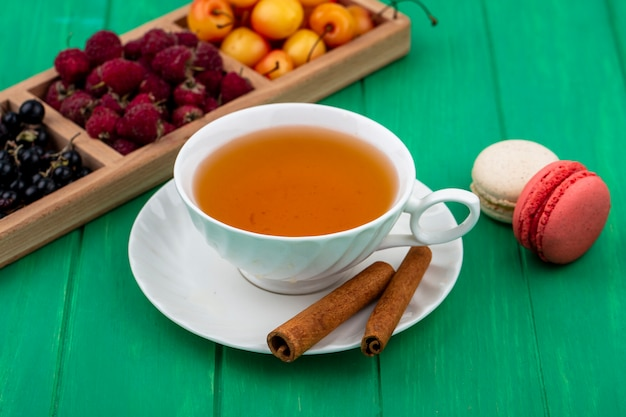 Vista frontal de uma xícara de chá com canela, framboesas, groselha preta, cerejas e macarons em uma superfície verde