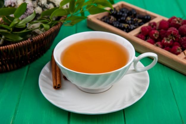 Vista frontal de uma xícara de chá com framboesas e groselhas pretas em uma superfície verde
