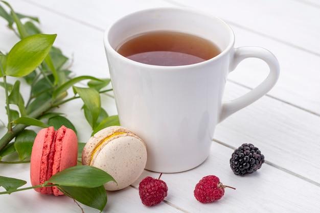 Vista frontal de uma xícara de chá com framboesas e macarons com galhos de folhas em uma superfície branca