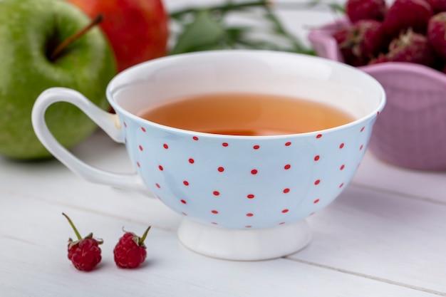 Vista frontal de uma xícara de chá com framboesas em uma superfície branca