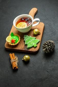 Vista frontal de uma xícara de cone de conífera de acessórios de xsmas de chá preto e limão de canela em uma tábua de madeira com fundo preto