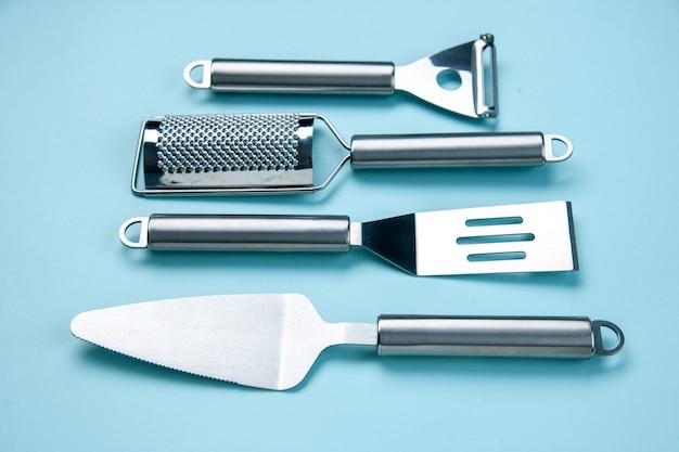 Vista frontal de utensílios de cozinha de aço inoxidável lado a lado em fundo de onda azul suave com espaço livre