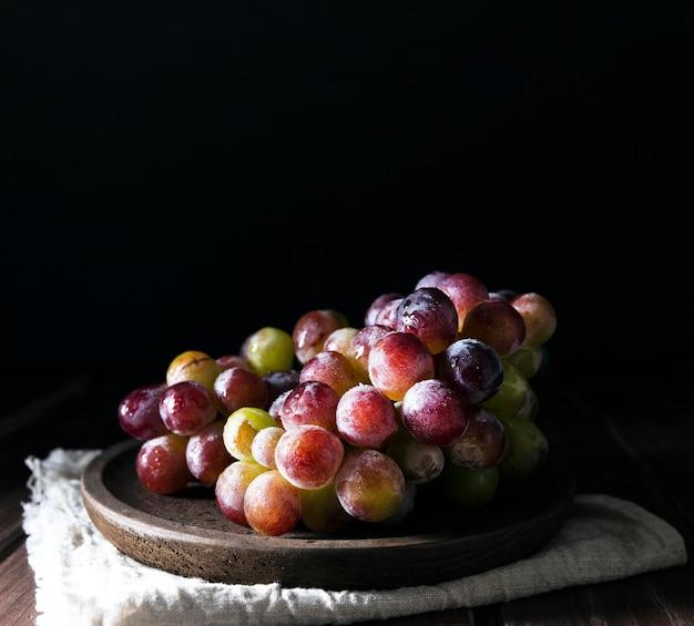 Vista frontal de uvas de outono no prato com espaço de cópia