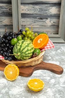 Vista frontal de uvas escuras frescas com laranja e melancia no fundo branco frutas maduras maduras árvore vitamínica fresca