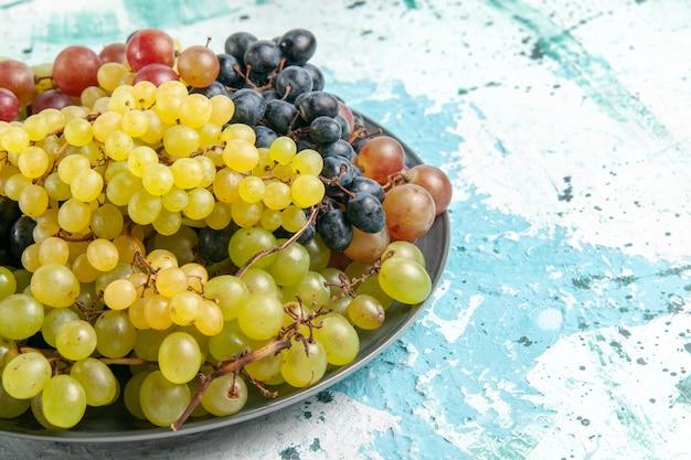 Vista frontal de uvas frescas coloridas frutas suculentas e maduras em superfície azul clara