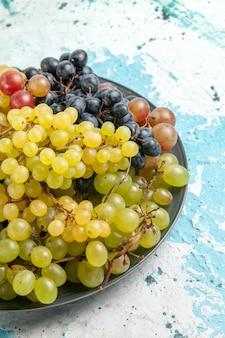 Vista frontal de uvas frescas coloridas frutas suculentas e maduras na superfície azul-clara