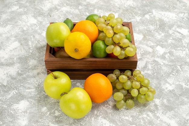 Vista frontal de uvas frescas com maçãs feijoa e tangerinas no fundo branco frutas maduras frescas cítricas exóticas Foto gratuita