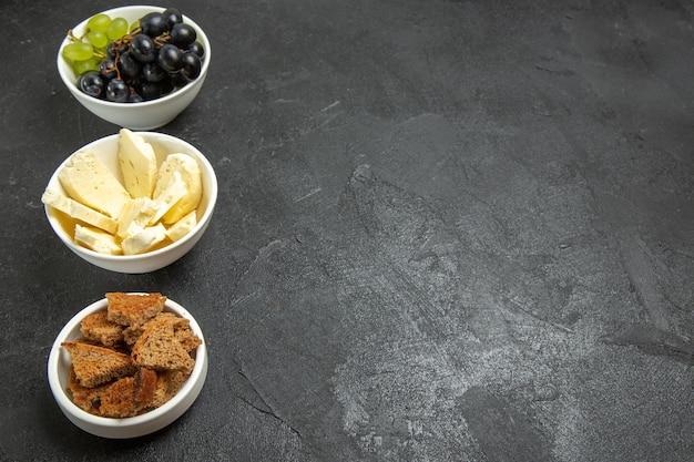 Vista frontal de uvas frescas com queijo branco e pão escuro fatiado no fundo escuro refeição prato de frutas leite