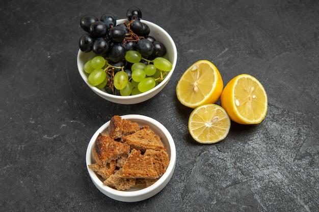 Vista frontal de uvas frescas com rodelas de limão no fundo escuro vitamina madura de frutas maduras