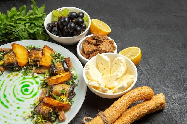 Vista frontal de uvas frescas e maduras com folhas de queijo branco e rolinhos de berinjela em fundo escuro refeição alimentos leite frutas