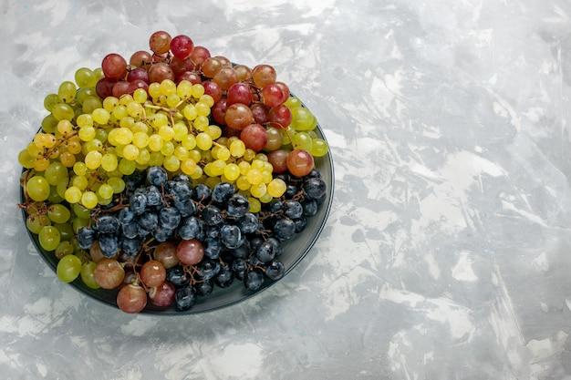 Vista frontal de uvas frescas frutas suculentas e maduras dentro do prato na superfície branca