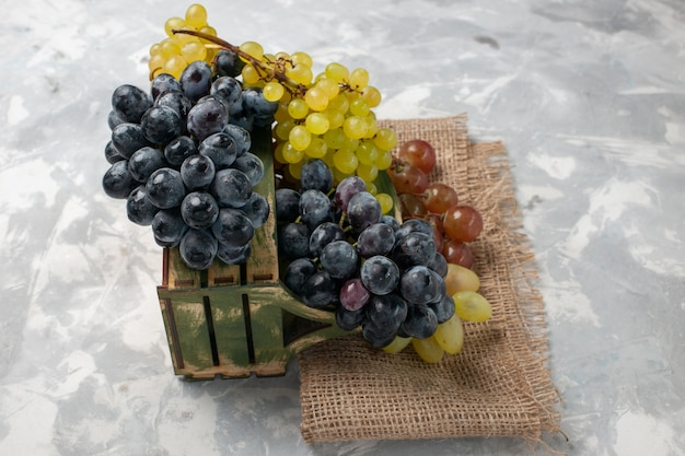 Vista frontal de uvas frescas frutas suculentas e maduras na mesa branca