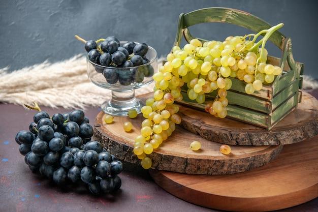 Vista frontal de uvas frescas, frutas verdes e pretas na superfície escura, uva, fruta madura, planta de árvore fresca