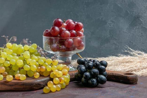 Vista frontal de uvas frescas maduras de cores diferentes na superfície escura vinho uva fresca planta árvore de fruta madura