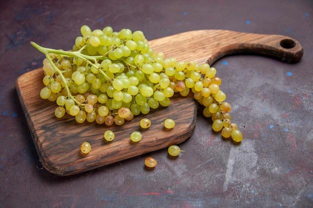 Vista frontal de uvas frescas maduras na superfície escura vinho uva fresca planta de árvore madura