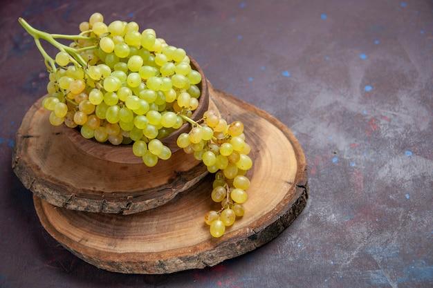 Vista frontal de uvas frescas maduras na superfície escura vinho uvas frescas plantas maduras