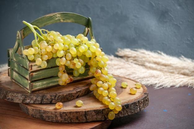 Vista frontal de uvas frescas verdes e frutas maduras na mesa escura vinho uva fruta madura planta de árvore fresca
