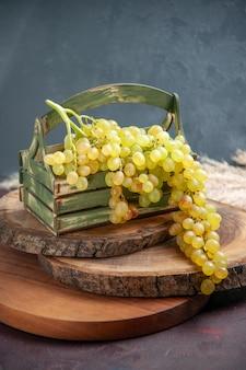 Vista frontal de uvas frescas, verdes e frutas maduras na superfície escura, uva, vinho, fruta madura, árvore fresca, planta