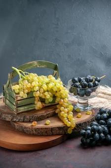 Vista frontal de uvas frescas, verdes e frutas maduras na superfície escura, uvas para vinho, frutas maduras, planta de árvore fresca