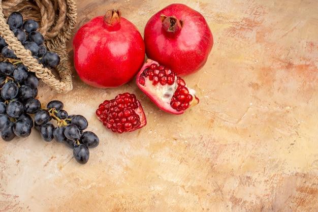 Vista frontal de uvas pretas frescas com romãs em fundo claro frutas maduras foto suave vitamina de árvore