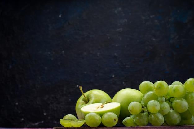 Vista frontal de uvas verdes com maçãs verdes no escuro