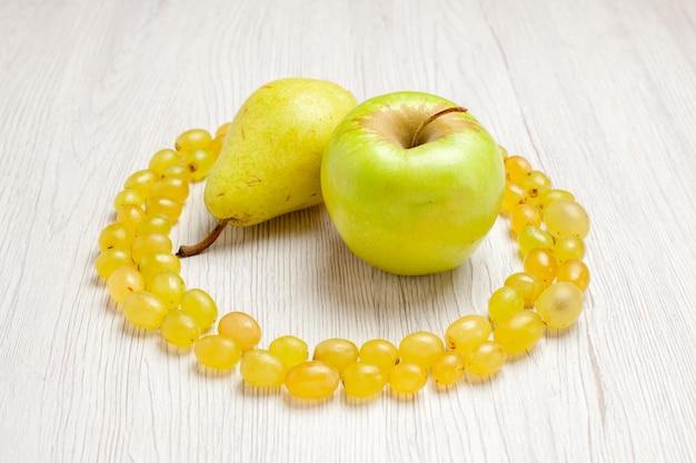 Vista frontal de uvas verdes frescas com pêra e maçã na mesa branca.