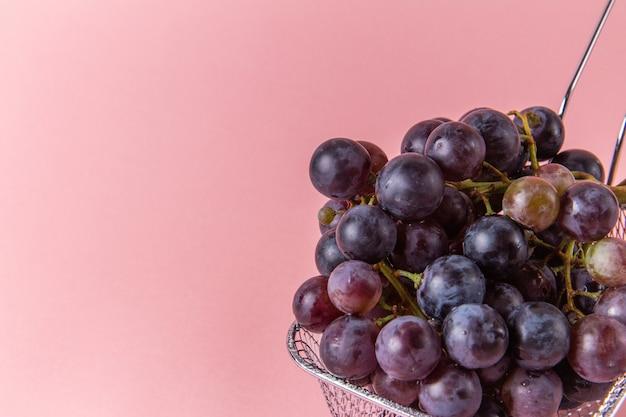 Vista frontal de uvas verdes frescas dentro da fritadeira na parede rosa