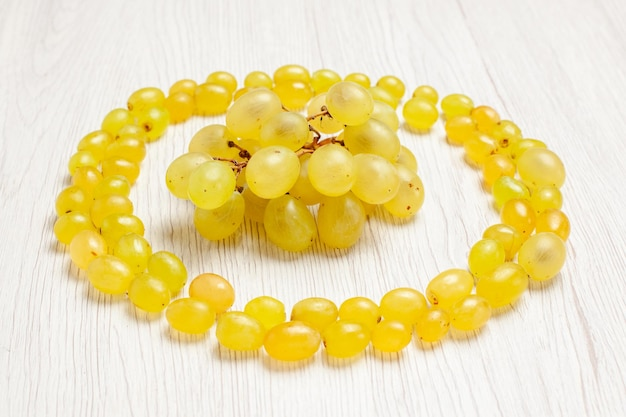 Vista frontal de uvas verdes frescas fazendo um círculo na mesa branca.