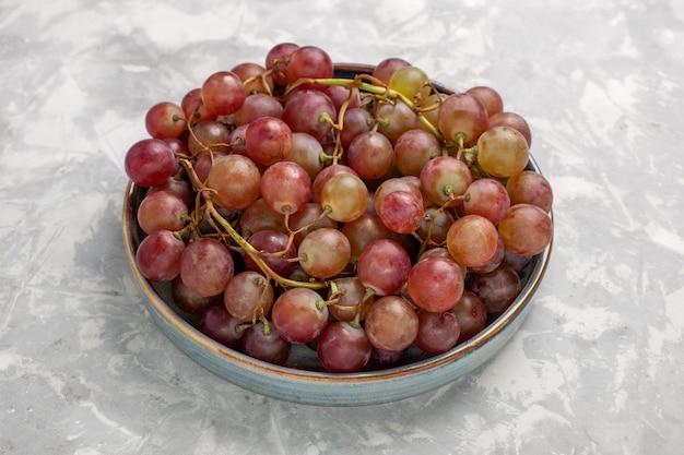 Vista frontal de uvas vermelhas frescas suculentas frutas suaves e doces na mesa branca clara