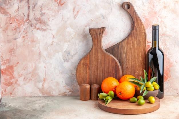 Vista frontal de vários tipos de tábuas de cortar de madeira e garrafa de vinho de frutas cítricas frescas no lado esquerdo na superfície colorida