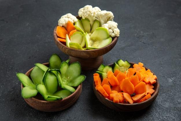 Vista frontal de vegetais de design diferente dentro de potes no espaço cinza