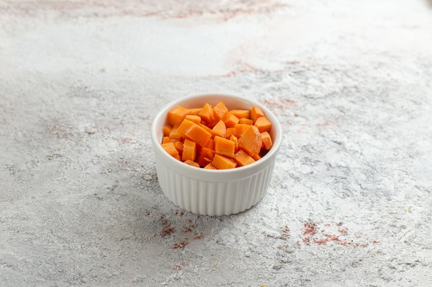 Vista frontal de vegetais em fatias de laranja dentro de uma pequena panela na superfície branca