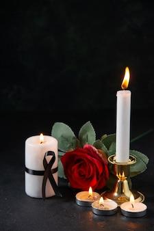 Vista frontal de velas acesas com flor vermelha na superfície escura