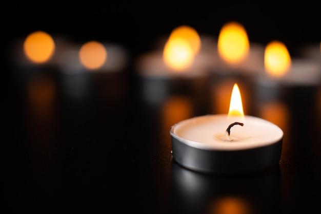Vista frontal de velas acesas na superfície escura como breu