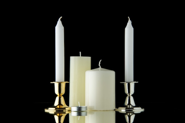 Vista frontal de velas brancas no escuro como breu