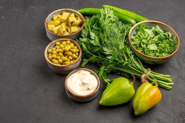 Vista frontal de verduras frescas com ingredientes de salada na superfície escura