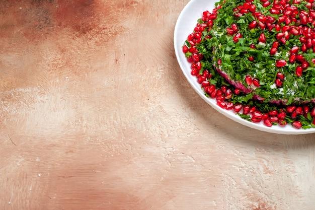 Vista frontal de verduras frescas com romãs descascadas na mesa clara de cor verde
