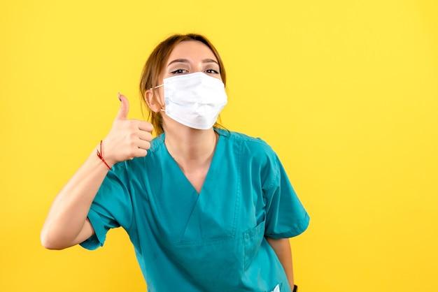 Vista frontal de veterinária usando máscara na parede amarela