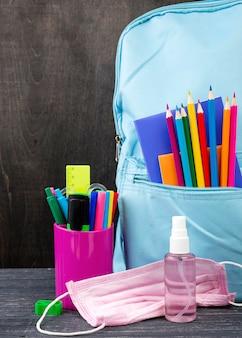 Vista frontal de volta aos artigos de papelaria da escola com máscara médica e desinfetante para as mãos