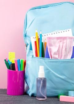 Vista frontal de volta para papelaria escolar com mochila e desinfetante para as mãos