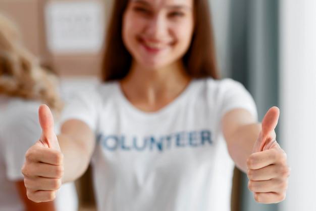 Vista frontal de voluntária desfocada fazendo sinal de positivo