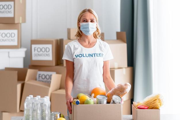 Vista frontal de voluntária segurando uma caixa de doação de alimentos