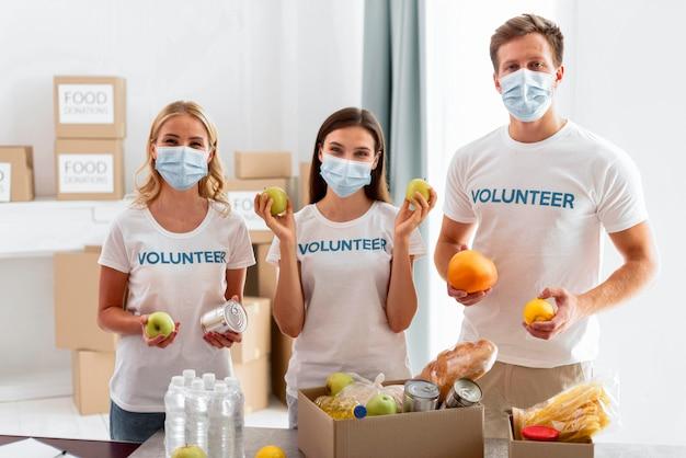 Vista frontal de voluntários com comida para doação