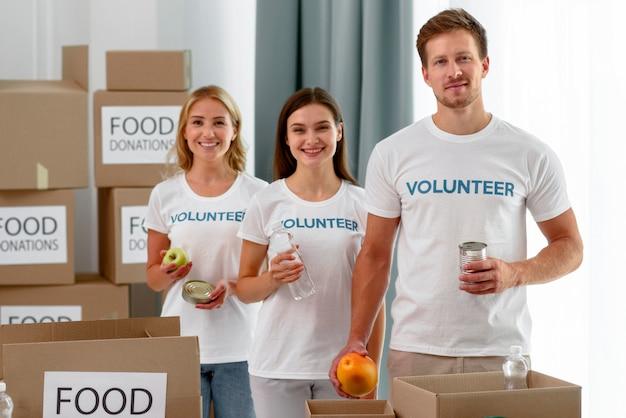 Vista frontal de voluntários posando enquanto ajudam com doações de alimentos