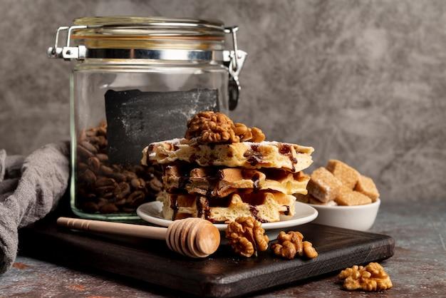 Vista frontal de waffles empilhados no prato com nozes e cubos de açúcar