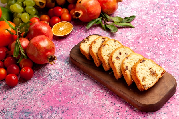 Vista frontal deliciosa composição de frutas com bolos fatiados na mesa rosa claro