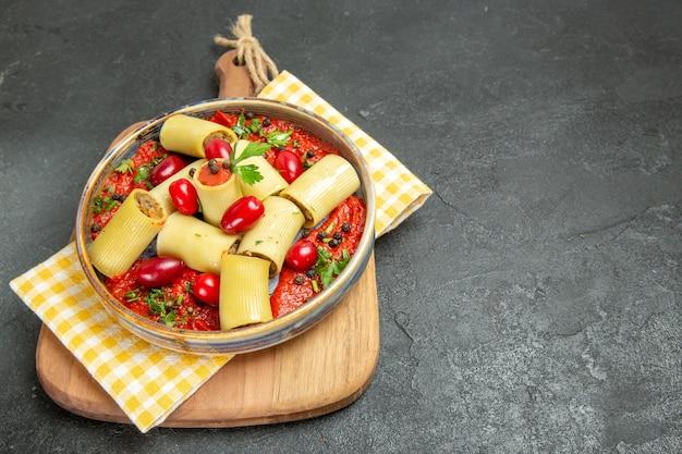 Vista frontal deliciosa massa italiana com carne e molho de tomate em fundo cinza