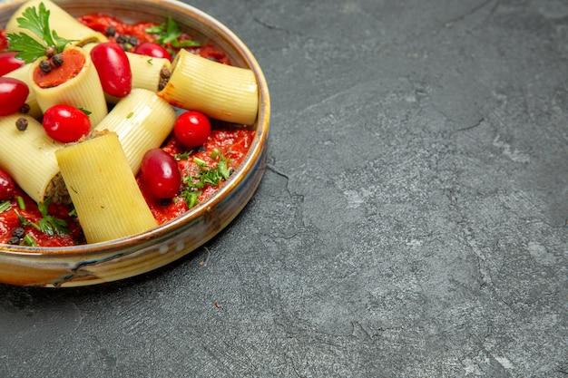 Vista frontal deliciosa refeição de massa italiana cozida com carne e molho de tomate em massa de piso cinza.