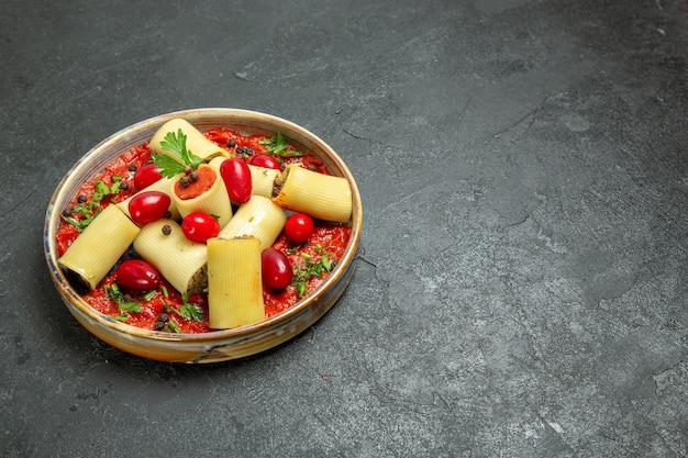 Vista frontal deliciosa refeição de massa italiana cozida com carne e molho de tomate no fundo cinza.