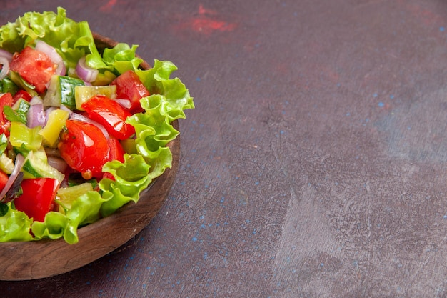 Vista frontal deliciosa salada de vegetais fatiada com ingredientes frescos em espaço escuro
